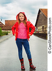 Vertical outdoor portrait of a cute little girl of 8-9 years old on a cloudy day, wearing bright red rain jacket and boots