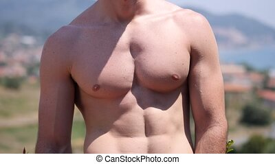 Vertical pan of shirtless athletic man