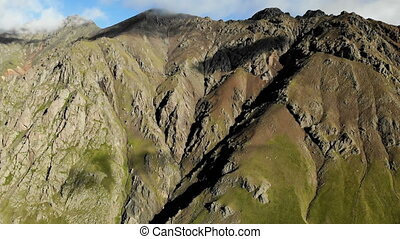 Vertical panorama of the rocky wall of the ridge. Flying...