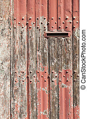 vertical part of old wooden door with letter box and bladdered red paint