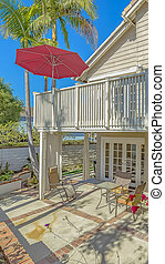 Vertical Patio with an eating area under the balcony with a red umbrella in the corner