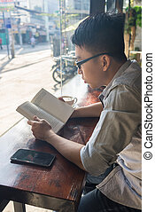 Asian man reading book in the coffee time