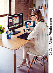 Vertical photo of attractive young photographer working with computer at the table and retouching with computer