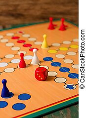 Vertical photo of Single red dice on Ludo board with several figurines. All placed on green old wooden table.