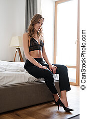 Vertical photo of woman sitting on bed
