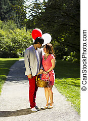 Vertical photo of young adult couple dressed in formal attire looking at each other while holding several balloons, picnic basket with walking path, green grass and trees behind them