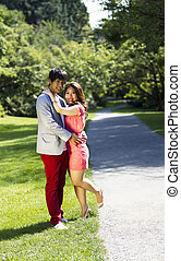 Vertical photo of young adult couple dressed in formal attire holding each other with walking path, green grass and trees behind them