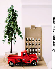 Vertical photo rendering with a red car. In the background there is a small tree and a house.