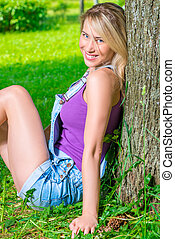 Vertical portrait of a beautiful blonde sitting near a tree in the park