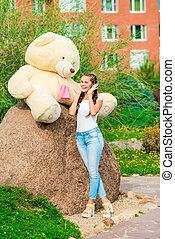 vertical portrait of a beautiful girl with a huge bear in the park