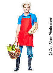 Vertical portrait of a farmer in full length with a crop of vegetables on a white background
