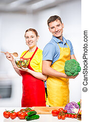 Vertical portrait of a happy couple with vegetables and salad in the kitchen