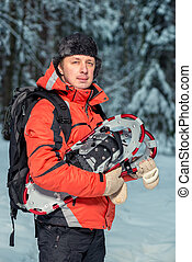 vertical portrait of a male tourist with snowshoes in the winter forest