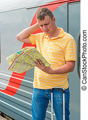 Vertical portrait of a man at the train station with map in hand