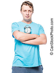 Vertical portrait of a man in pajamas with an alarm clock on white background