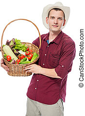 Vertical portrait of a man with a basket of ripe vegetables on a white background