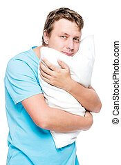 Vertical portrait of a man with a soft pillow on a white background