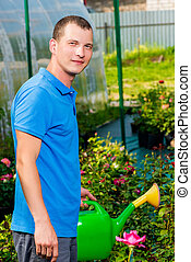 Vertical portrait of a man with a watering can in a garden watering flowers