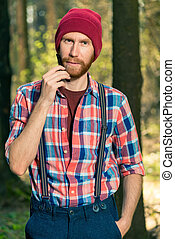 vertical portrait of a rural bearded man in a forest, a man combing his beard