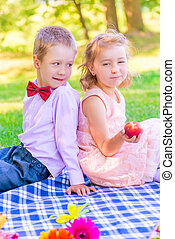 Vertical portrait of a six-year old couple at a picnic in the park