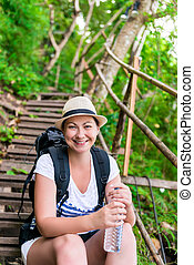 vertical portrait of a tourist with a bottle of water on the stairs