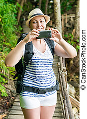 vertical portrait of a tourist with a phone and a backpack on a trail in the jungle