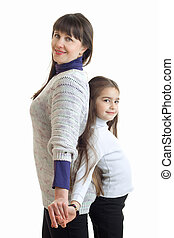 vertical portrait of a young mom that stands in the Studio with her daughter