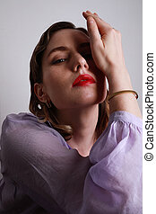 Vertical portrait of beautiful young woman in purple shirt posing with hand up on the white background.