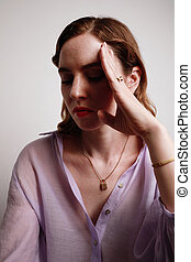 Vertical portrait of young woman in purple shirt posing with hand up on the white background.