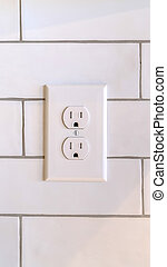 Vertical Power outlet on white wall in home