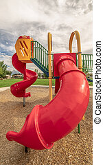 Vertical Red closed tube slide and spiral slide at a playground against cloudy blue sky