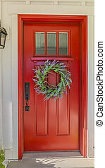 Vertical Red front door of modern home with green wreath