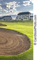 Vertical Sand trap and fairway of a golf course with lake front houses in the background