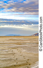 Vertical Sandy shore of a lake and distant rugged mountain under cloudy blue sky