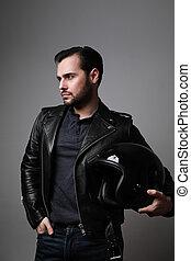 Vertical shot of brutal bearded biker man holding helmet dressed in a black leather jacket. Free space for text.