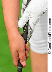 Vertical shot of female hands with a golf club on the pitch