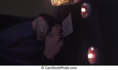 Vertical shot of middle-aged woman witch shuffles fortune-telling cards in her hands while sitting at a dark table with a candles. Concept of black magic and fortune telling