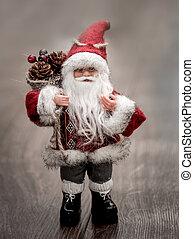 Santa Claus statuette on grey background in blur.
