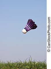 Shuttlecock in action in grass against a bright blue sky