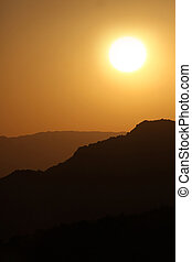 Vertical Silhouette Sunrise of Hazy Misty Mountains With Warm Colors