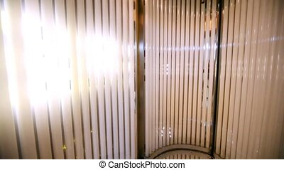 Vertical solarium stands with an open door and is shown...