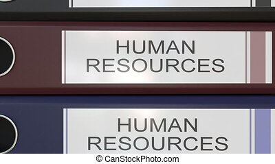 Vertical stack of multicolor office binders with Human resources tags