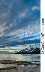 Vertical Striking cloudy sky over a calm lake that reflects the golden sun at sunset