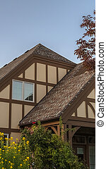 Vertical Unusual timber frame house with double apex roof