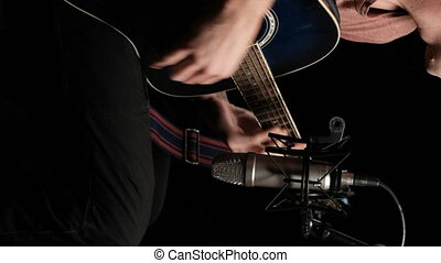 Vertical video: Acoustic guitar recording on studio microphone on black background. Young man blogger sitting on chair and plays the guitar, filming himself for social networks. Sound recording studio