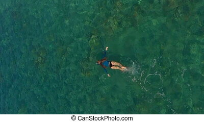 Vertical video. Aerial shot of a woman snorkeling in a beautiful turquoise sea
