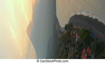 Vertical video. Aerial shot of the beautiful Jemeluk bay in the Amed area with the view on a marvelous Agung volcano. Sunset in Amed. Travel to Bali concept.