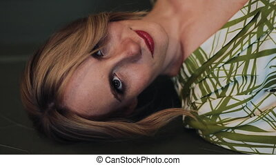 Vertical video. Portrait of beautiful pregnant woman in green dress looking and posing into the camera. Slow motion. Vertical frame for mobile devices