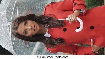 Vertical video. Portrait of smiling attractive woman standing on the street with umbrella while it is raining. Happy cute beautiful fashion water girl summer face female close up slow motion