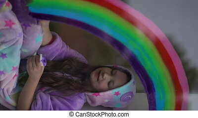 vertical video. school girl in pajamas draws the rainbow on the window at home. Stay home, flash mob chase the rainbow.